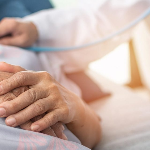 Hospitalized elderly patient woman laying on bed with cardiologist doctor or physician examining heart health, checking pulse in hospital clinic exam room